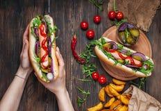 Hot dog nelle mani delle donne su una tavola di legno top Fotografie Stock