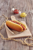 Hot dog. With onion, ketchup and mustard on a white chopping board on a wooden table. Ketchup and mustard in two transparent bowls Royalty Free Stock Images