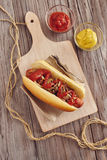 Hot dog. With onion, ketchup and mustard on a white chopping board on a wooden table. Ketchup and mustard in two transparent bowls Royalty Free Stock Photography