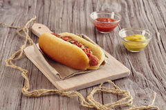 Hot dog. With onion, ketchup and mustard on a white chopping board on a wooden table. Ketchup and mustard in two transparent bowls Royalty Free Stock Photos