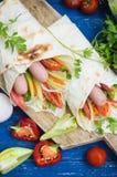 Hot dog - panino con la salsiccia in pita, carote coreane, pomodori, cipolle, prezzemolo e pepe Priorità bassa di legno Fotografia Stock