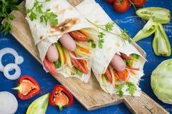 Hot dog - panino con la salsiccia in pita, carote coreane, pomodori, cipolle, prezzemolo e pepe Priorità bassa di legno Fotografia Stock Libera da Diritti