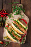 Hot dog with pickles, capers and arugula Royalty Free Stock Photography