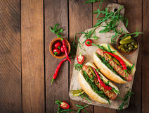Hot dog with pickles, capers and arugula Royalty Free Stock Images