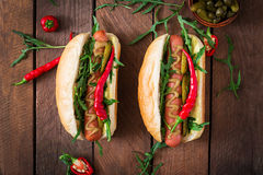 Hot dog with pickles, capers and arugula Royalty Free Stock Photo