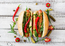 Hot dog with pickles, capers and arugula Stock Photo