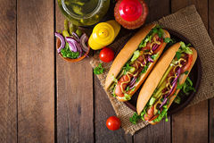 Hot dog with pickles, tomato and lettuce on wooden background. Royalty Free Stock Images