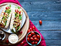Hot dog with pickles, tomatoes and olives. Hot dog with pickles, tomatoes, olives and lettuce  on wooden background. Top view Royalty Free Stock Photo