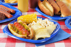 Hot dog with relish on a summer cookout. A hot dog with macaroni salad, chips and corn on the cob on a picnic table Stock Image