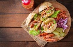 Hot-dog - sandwich avec des conserves au vinaigre, des oignons rouges et la laitue sur le fond en bois Photographie stock