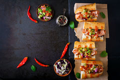 Hot dog - sandwich with Mexican salsa on dark background. Stock Photos