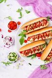 Hot dog with sausage. bacon, cucumber, tomato and red onion. On white plate. Top view. Flat lay Stock Photos