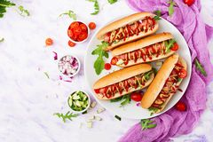 Hot dog with sausage. bacon, cucumber, tomato and red onion. On white plate. Top view. Flat lay Stock Image