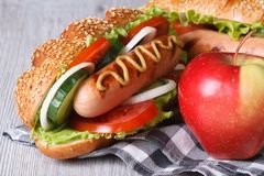 Hot dog with sausage and red apple close-up Stock Photo
