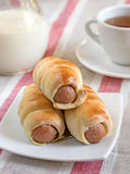 Hot-dog with sausages in a plate with tea and milk. Hot-dog with sausages on a table with milk and tea stock photography
