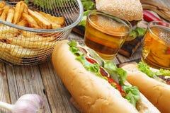 Hot dog, spuntini differenti e birra su una tavola di legno, primo piano Hot dog U.S.A. di festa nazionale Fotografia Stock Libera da Diritti