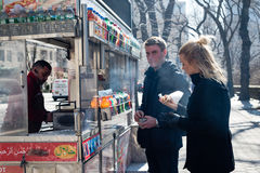 Hot Dog Stand and Young Couple in Central Park - New York City. Young blonde couple gets a hot dog from a food truck in Central Park while on vacation in New Stock Images