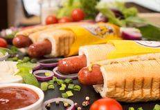 Hot dog sull'ardesia nera con le verdure Fotografia Stock