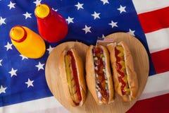 Hot-dog sur le conseil en bois de forme de coeur avec le thème du 4 juillet Image stock