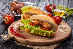 Hot dog with Tomato, lettuce, Sausage, mustard, ketchup Stock Photo