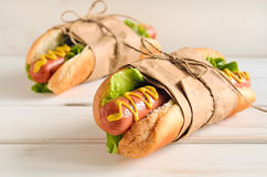 Hot dog. Two hot dogs with american yellow mustard and fresh lettuce rolled in a paper and knotted with bow on a light wooden background. Good as a present for Stock Photography