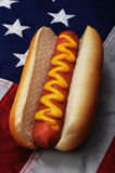 Hot dog and US flag. Closeup of a hot dog on a bun with mustard and an American or US flag in the background Royalty Free Stock Images