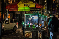 Hot dog vendor serving a customer from his cart on a nighttime Manhattan sidewalk Royalty Free Stock Image