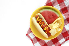 Hot dog with watermelon and chips. On a yellow plate with a red and white plaid napkin on white wood background Stock Image