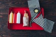 Hot dog z musztardą, ketchupem i majonezem na drewnianym tle, Odgórny widok Obrazy Stock