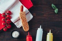 Hot dog z musztardą, ketchupem i majonezem na drewnianym tle, Odgórny widok fotografia stock
