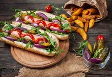 Hot dog z na pokładzie kumberlandu i francuza dłoniaków na drewnianym stole Obraz Stock