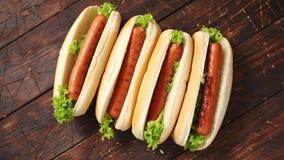 Hot-dogs américains savoureux assortis dans la rangée Placé sur le Tableau en bois banque de vidéos