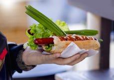 Hot-dogs avec la tomate, conserves au vinaigre, oignons dans une main sur la rue image stock