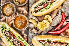 Hot dogs, beer, chips on wooden table in the pub. Top veiw royalty free stock photo