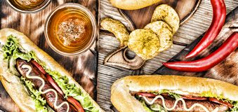 Hot dogs, beer, chips on wooden table in the pub. Top veiw stock images