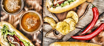 Hot dogs, beer, chips on wooden table in the pub. Top veiw royalty free stock images