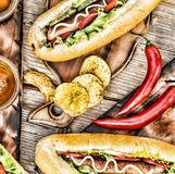 Hot dogs, beer, chips on wooden table in the pub. Top veiw royalty free stock photography