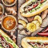 Hot dogs, beer, chips on wooden table in the pub. Top veiw stock photos