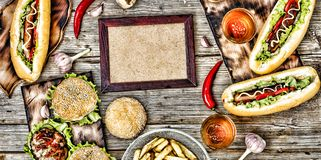Hot dogs and beer on a wooden table. Rustic style, top view homemade burgers with beef. Rustic style, top view homemade burgers with beef, hot dogs and beer on a stock photo