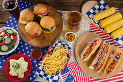 Hot dogs and burgers on wooden table with 4th july theme Royalty Free Stock Photos