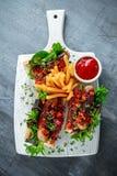 Hot-dogs de saucisse de Cumberland à l'oignon caramélisé, poivrons rouges rôtis, pommes frites Photo libre de droits