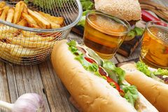 Hot dogs, Different snacks and beer on a wooden table, close-up. National Day hot dog USA. Fast food royalty free stock photo