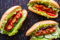 Hot dogs of different tastes on a black background Stock Photos