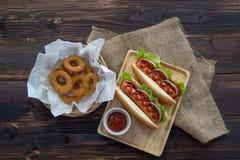 Hot dogs et anneaux d'oignon frits, admirablement disposé, appétissants sur la table de salle à manger en bois brune image libre de droits