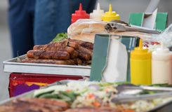 Hot dogs fast food on street. Street vendor`s cart offering hot dogs, buns and stirred fried vegetables Royalty Free Stock Images