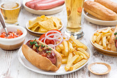 Hot dogs with French fries, beer and snacks. Horizontal stock photo