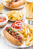 Hot dogs with French fries, beer and snacks, vertical, top view. Close-up royalty free stock photo