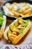 Hot Dogs with french fries in the skillet on wooden background Stock Photos