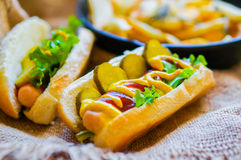 Hot Dogs with french fries in the skillet on wooden background Royalty Free Stock Images