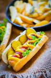 Hot Dogs with french fries in the skillet on wooden background Stock Images
